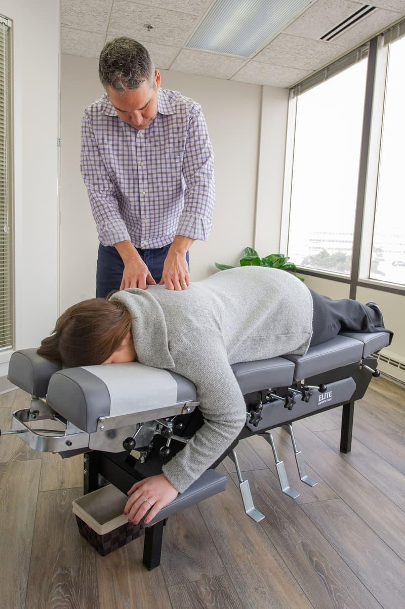 Chiropractor at West Suburban Wellness adjusting patient
