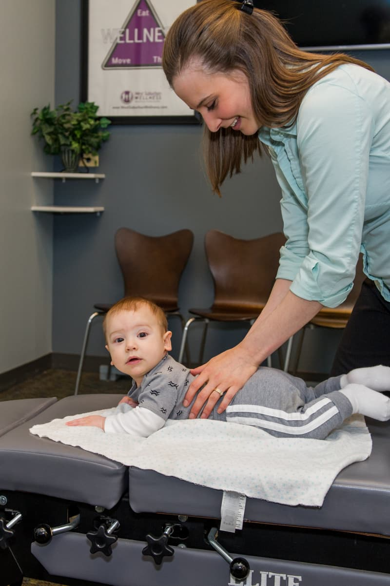 Doctor of Chiropractic adjusting a baby