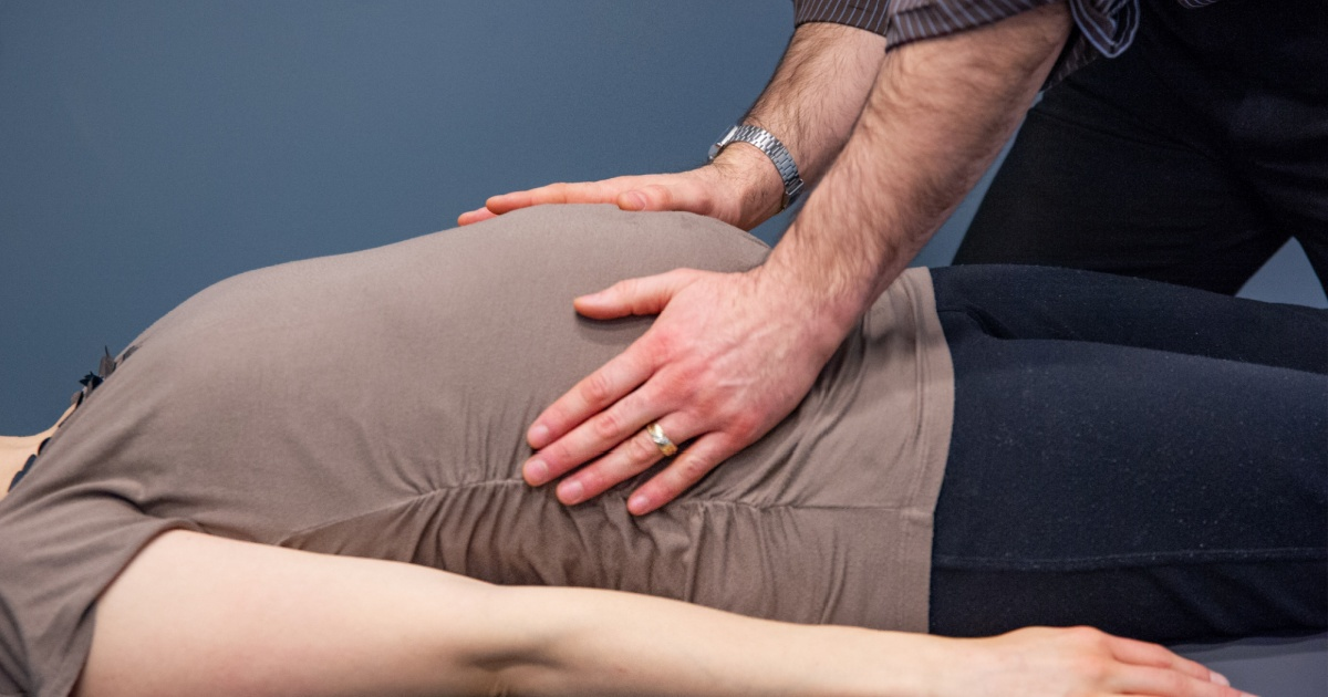 pregnant woman with chiropractic doctor hands on belly